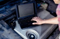 Car mechanic with laptop checking enine