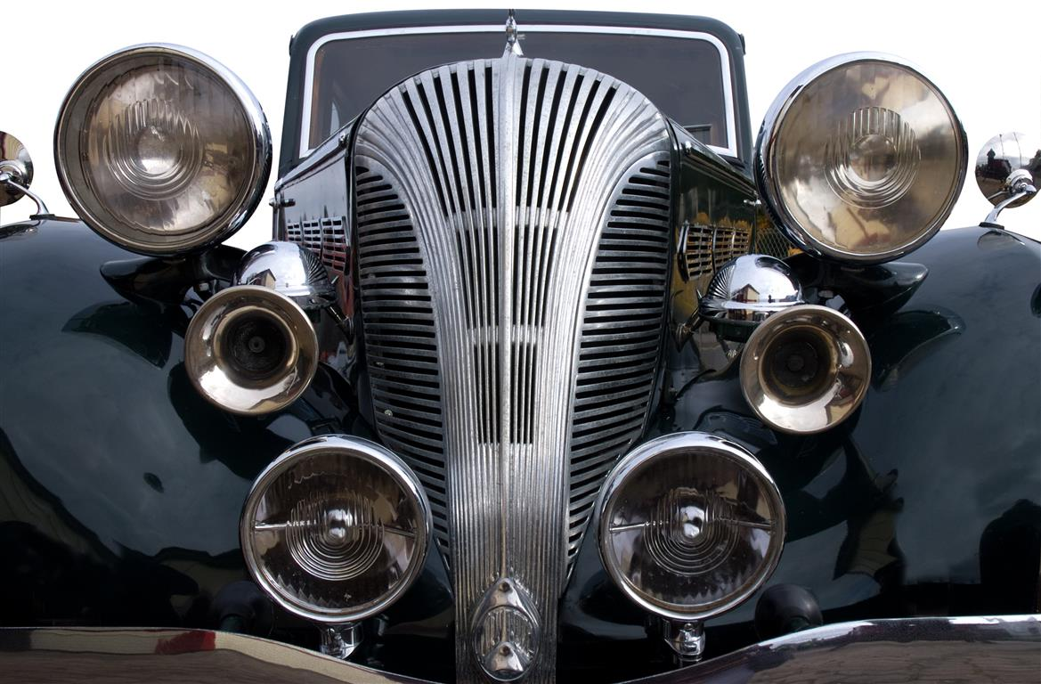 A vintage black car with lights and chrome horn