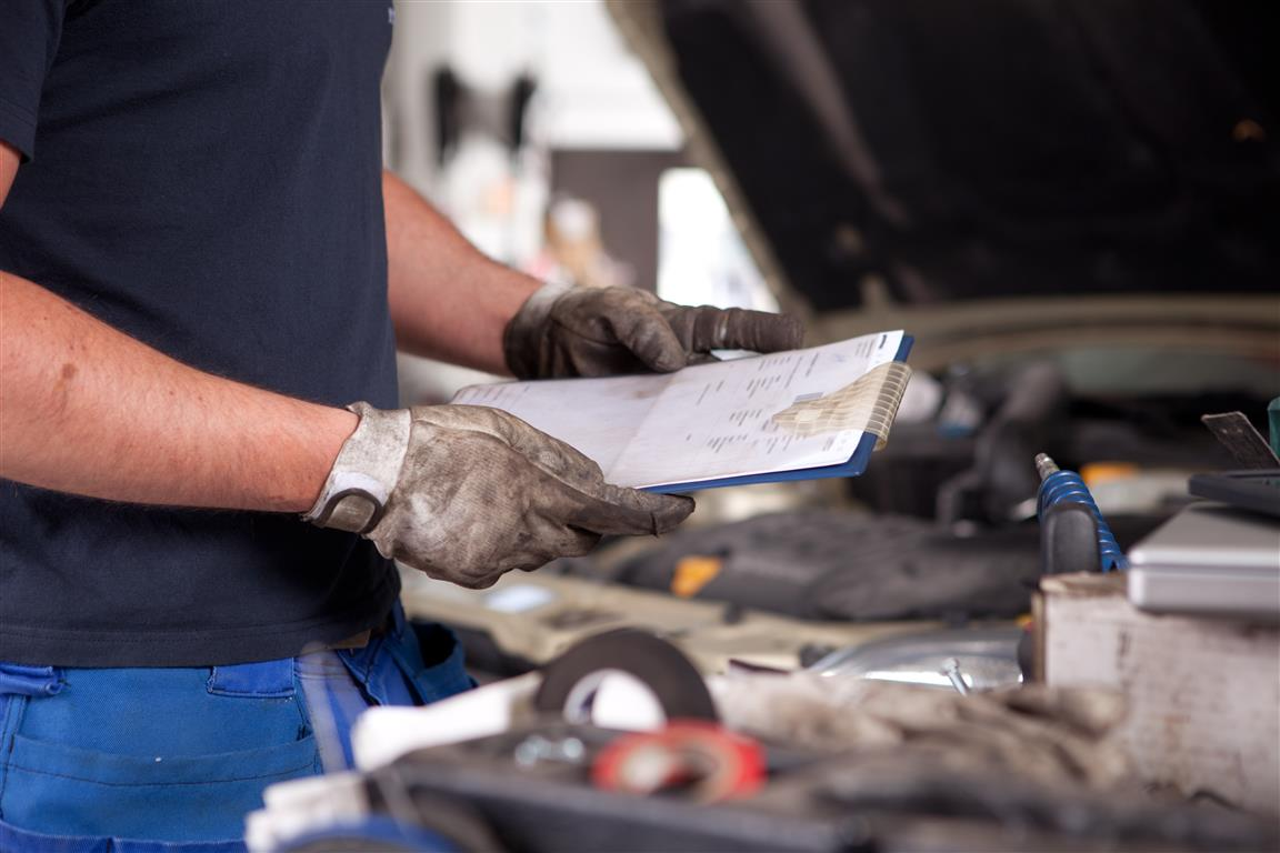 Detail of a mechanic holding a service order with a dirty glove on